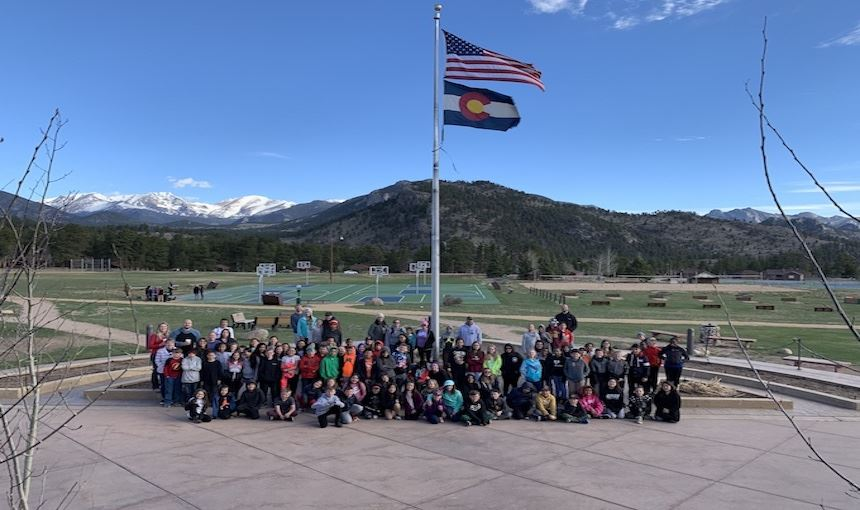 Fifth grade students standing under the flag with the mountains in the background.