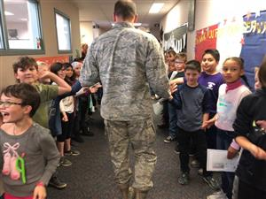 Students high five military members.