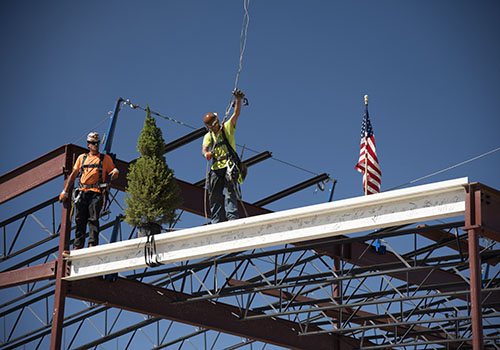 "Workers install a steel beam during a ""Topping Out"" ceremony on Sept. 14"