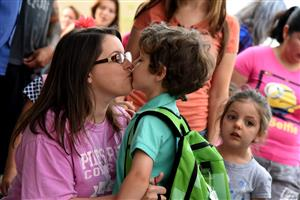 Mom gives kisses to her child on the first day of school.