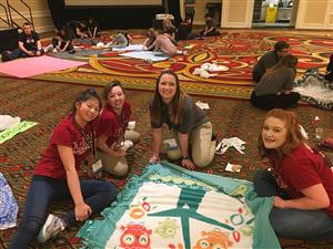 May Bombria (16), Fayth Smith (16), Kierstin Estepp (17), and Chai Bensenberg (17) stop to show the blanket they were making