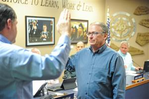 John Koster (right) takes the oath to serve on the D49 Board of Education Jan. 22
