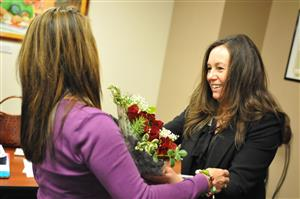 Kathleen Granaas presents a bouquet to Malou Koster as she is recognized during Fantastic 49 Dec. 12.