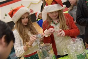 Cali Zahn and Emma Schlosser, HMS students, prepare the ornament making station at the holiday party Dec. 14.