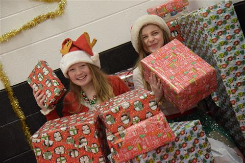 Cali Zahn and Emma Schlosser, HMS students, prepare stacks of presents at the holiday party Dec. 14.
