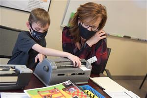Lori Mattick, teacher of the visually impaired, watches as Cameron Hames demonstrates the braillewriter.