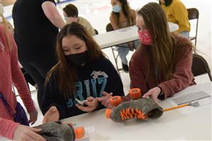 A team of SSAE girls reassembles a skate March 10 during a STEM presentation at Skate City.