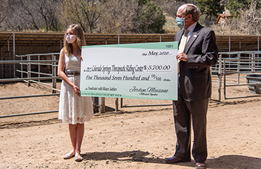 Jordyn Maisano, PPEC freshman, and Mayor John Suthers present a check to a local riding center.