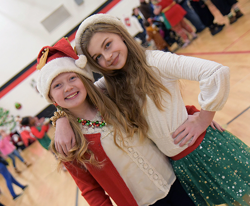 Cali Zahn and Emma Schlosser, sixth-graders at HMS, help host holiday party Dec. 14.