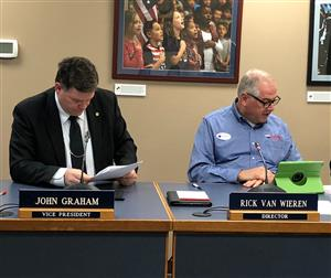 BOE members John Graham and Rick Van Wieren review materials during the Dec. swearing in ceremony