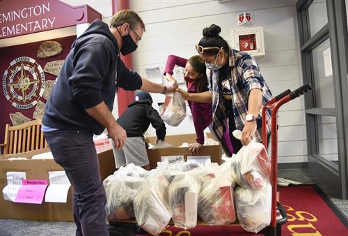 Volunteers move food bags