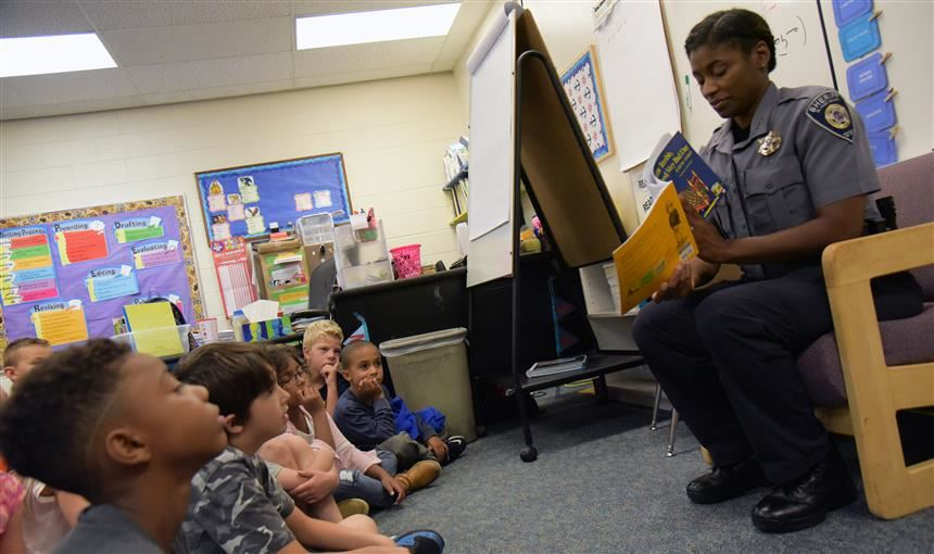 Law enforcement officer reads to students at Falcon Elementary School of Technology Sept. 13.