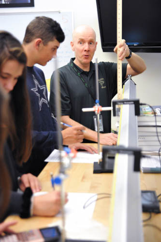 FHS Math and Physics teacher Tim Cerniglia discusses a physics experiment with students during a classroom assignment Sept 16