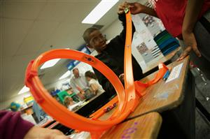 Dereon Harris, RES fourth-grader, adjusts a ramp to get a toy car to complete a loop in the track on STEM Night