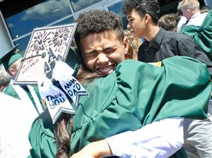 FHS Grad hugs a friend after graduation ceremony May 25