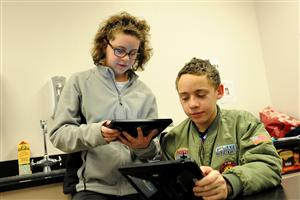Eighth-grader Alyssa Dowdy, 14, helps Riley Dowdy, 14 write an email to a member of the International Astronomical Union.