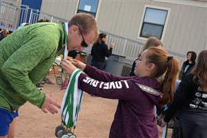 A race participant receives his medal after the D4.9K Run/Walk, Sat., Nov. 4 at Stetson Elementary School.