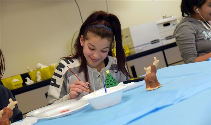 Girl paints her holiday piece during ceramics session at mini course day at FMS Thurs., Nov. 16.