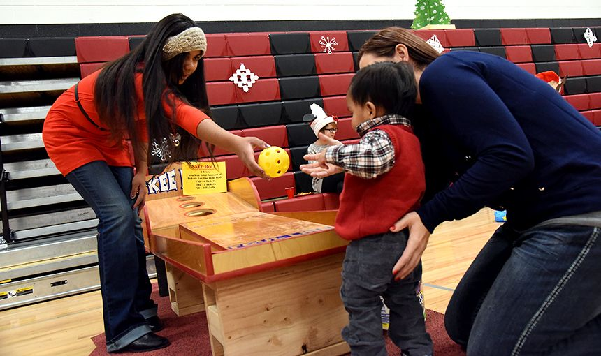 Isabela Goodridge, HMS seventh-grader, helps a foster child and parent play skee-ball Dec. 10.
