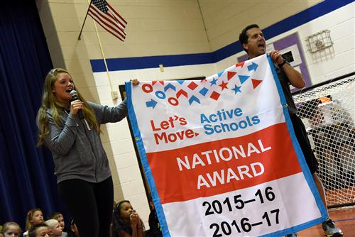 Professional soccer player Andi Tostanoski and Matt Monfre, PE teacher, present SES students the Let's Move award.