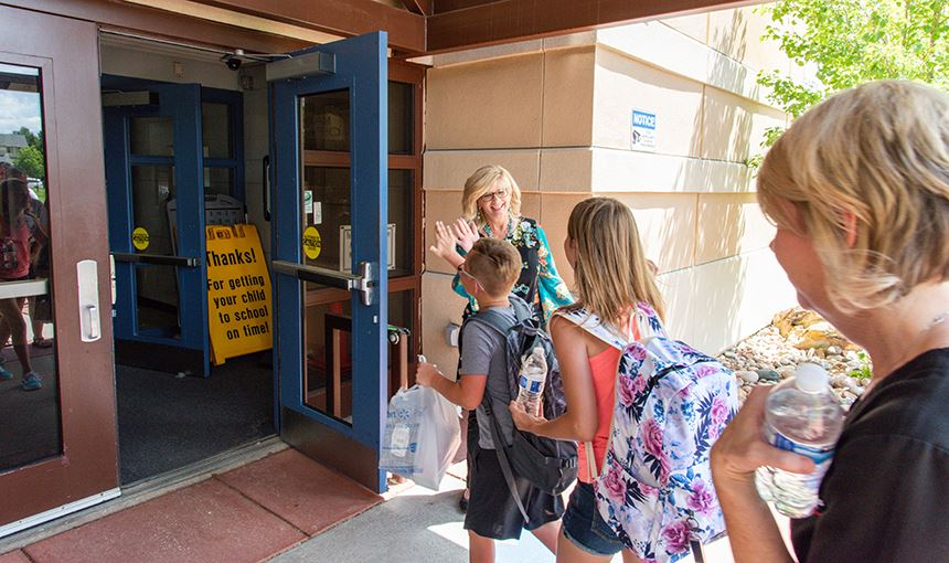 Kim Moore, Principal, greets students and families as they are welcomed back to the school.