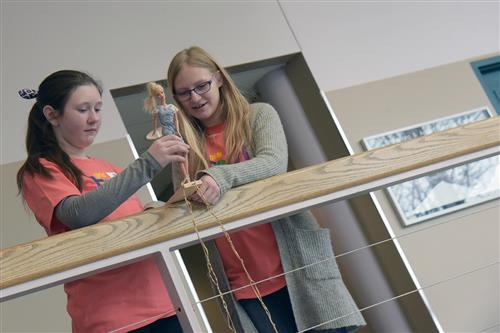 Girls send their doll over the edge during the Bungee Barbie experiment at the Girls' STEM Experience at UCCS Feb. 1.