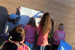 "Firebird Ambassadors hang posters outside the school to promote the ""walk up"" at Falcon Middle School March 14."