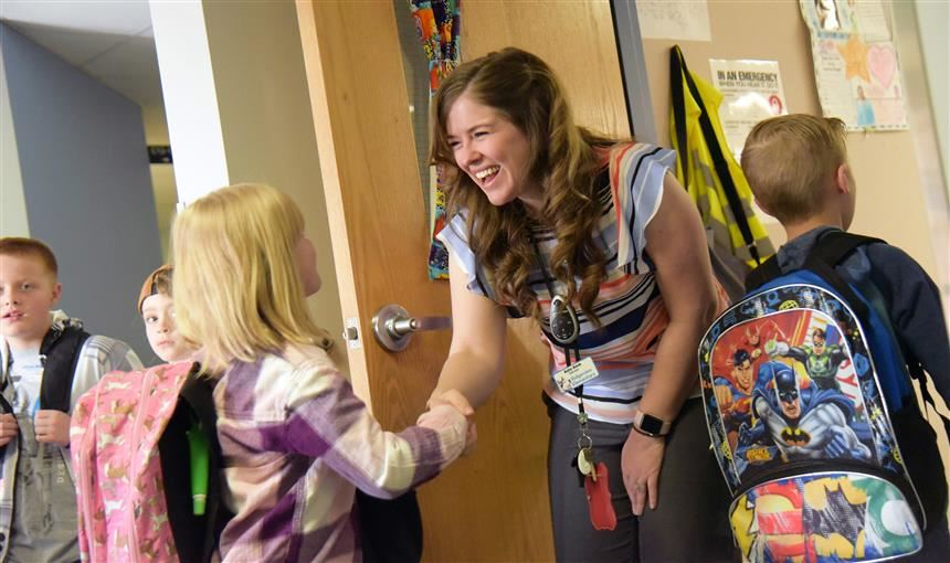 Kate Bock, first grade teacher, personally greets students outside her classroom at RVES April 5.