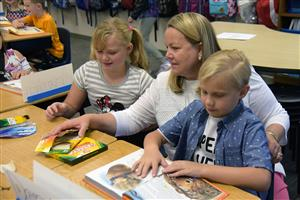JoAnne Gebhardt, third grade teacher, helps students get settled in on the first day of class at WHES Aug. 2.