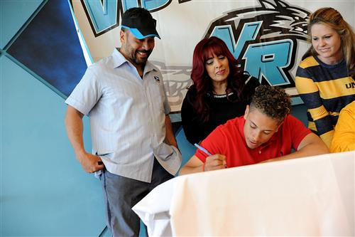 Twelfth-grader Louis Quinones, 18, signs a letter of intent.