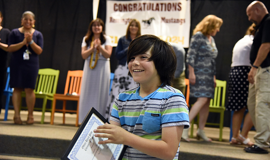 Hunter Romero, 11, walks back to his seat May 25 after receiving the Pratt Citizenship Award at RES