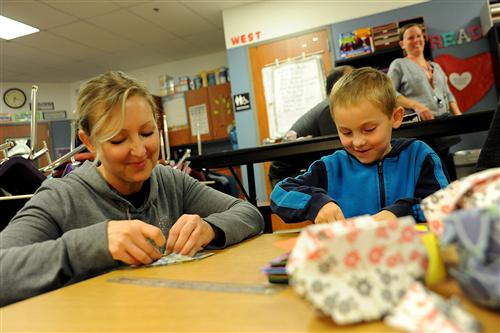 Amy Newby and second-grader Grant Newby, 7, create origami balloons.
