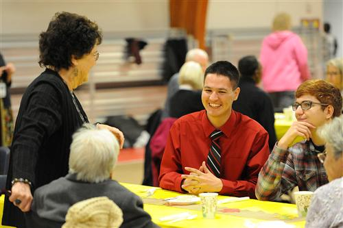 Twelfth-grader Donovan Spencer, 17, shares a meal with senior citizens during a Thanksgiving feast.