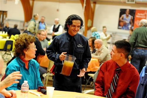 Eleventh-grader Josiah Santiago, 16, serves students and senior citizens during a Thanksgiving feast.