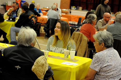 Twelfth-grader Deanna Meyer, 18, shares a meal with senior citizens during a Thanksgiving feast.