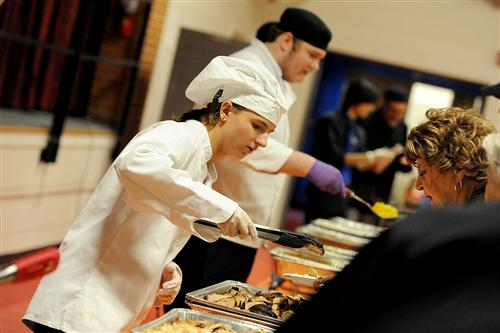 Tenth-grader Ayden Marshall, 16, serves meals to senior citizens during a Thanksgiving feast.