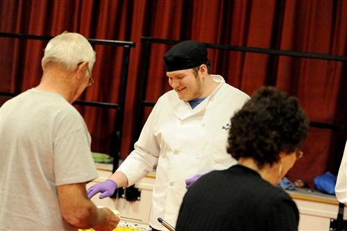 Twelfth-grader Ryan Worden, 17, serves meals to senior citizens during a Thanksgiving feast.