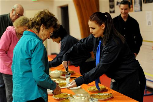 Eleventh-grader Abigail Gordon, 16, serves dessert to senior citizens during a Thanksgiving feast.