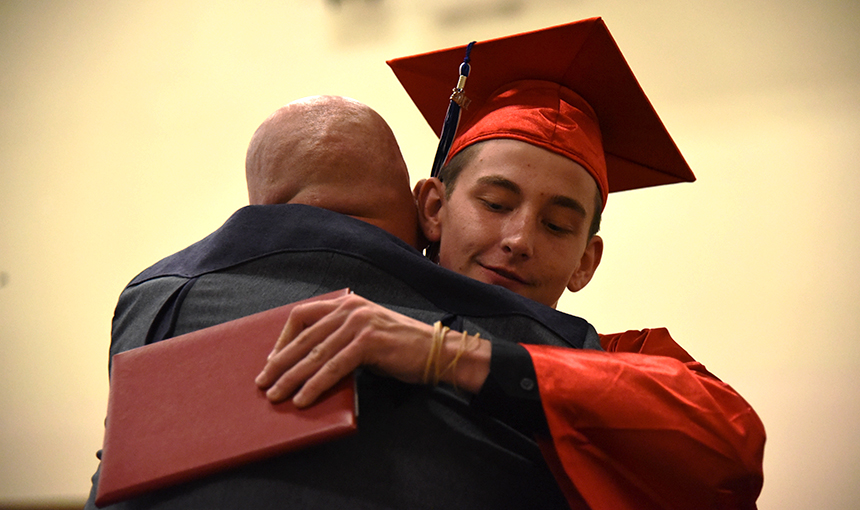 A PHS graduate hugs Greg Cox, dean of students, after receiving his diploma May 25.