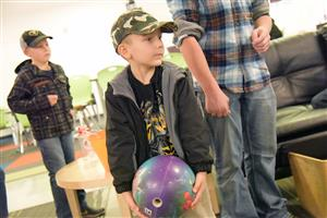 A sibling of an SSAE student tries his luck bowling at the Harvestmania event Nov. 9 at Springs Studio.