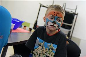 Gavin Malo, third-grader at SSAE, patiently waits for his face painting to be complete at Harvestmania Nov. 9.