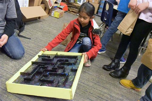 June Talain, second-grader, tests her skills on a maze game at the Woodmen Hills Elementary School cardboard arcade Nov. 28.