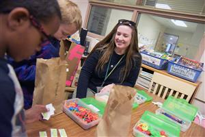 Mary Hopper, project-based learning teacher at WHES, helps students redeem tickets at the cardboard arcade Nov. 28.