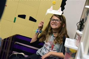 Maddie Lavelle, fifth-grader, poses in the photo booth at the cardboard arcade at WHES Nov. 28.