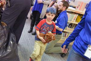 A kindergartner receives a teddy bear at the Badges and Books event at WHES Jan. 11.