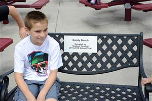 "Fifth-grader Jake Amaya, 11, sits on a ""Buddy Bench""."