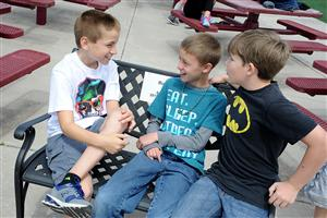 "Fifth-graders Jake Amaya, 11, Tristan Gunderson, 11, and Owen Lee, 10, sit on a ""Buddy Bench""."
