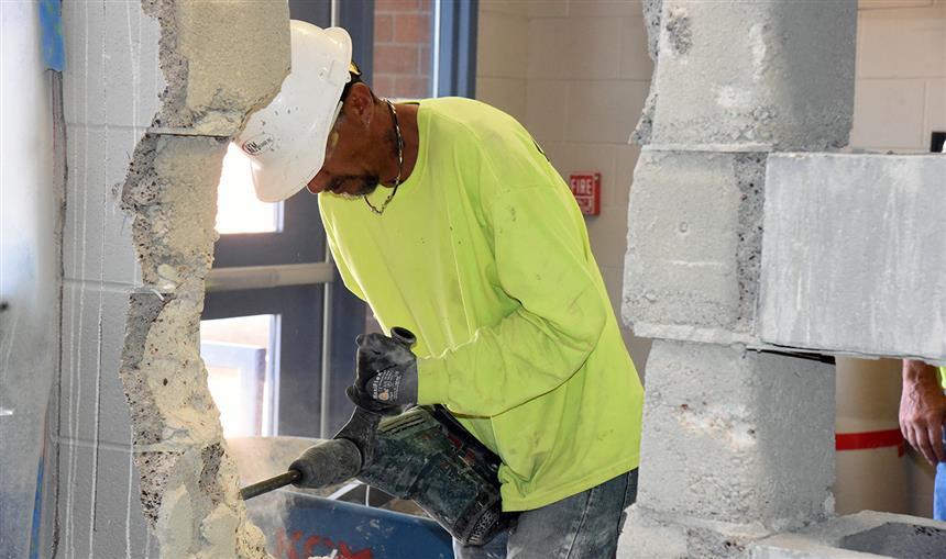 A Nunn Construction worker demolishes a wall at the entrance of Sand Creek High School.