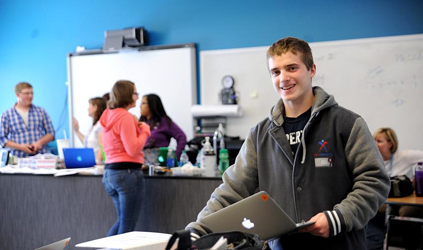 Jay Barnish, a senior at Falcon Virtual Academy, grabs a computer April 21.