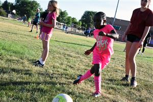 "Malia Fudge, 6, first grader at EIES, kicks the ball down field at ""kick around."""